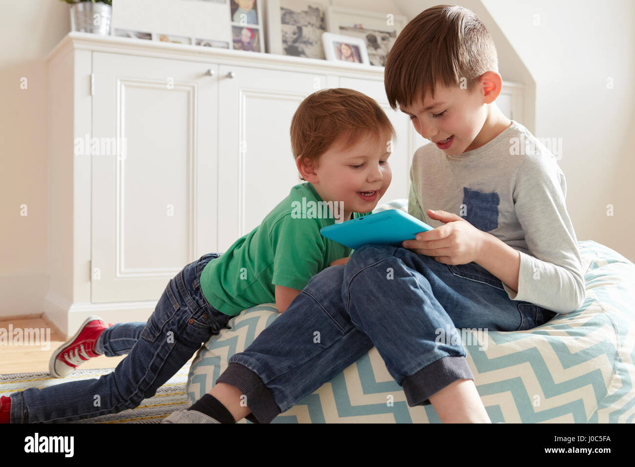 Male toddler and brother on beanbag chair looking at digital tablet - Stock Image
