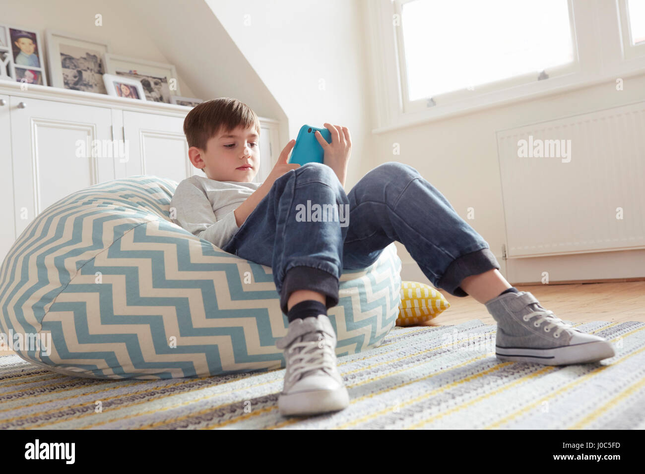Boy reclining on beanbag chair looking at digital tablet - Stock Image