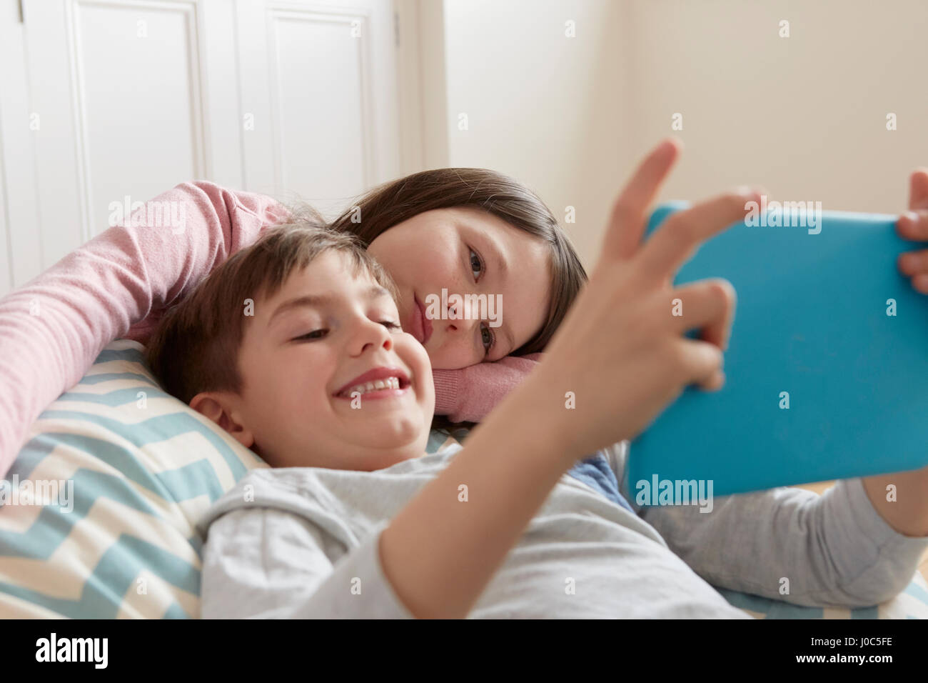 Boy and sister reclining on beanbag chair looking at digital tablet - Stock Image