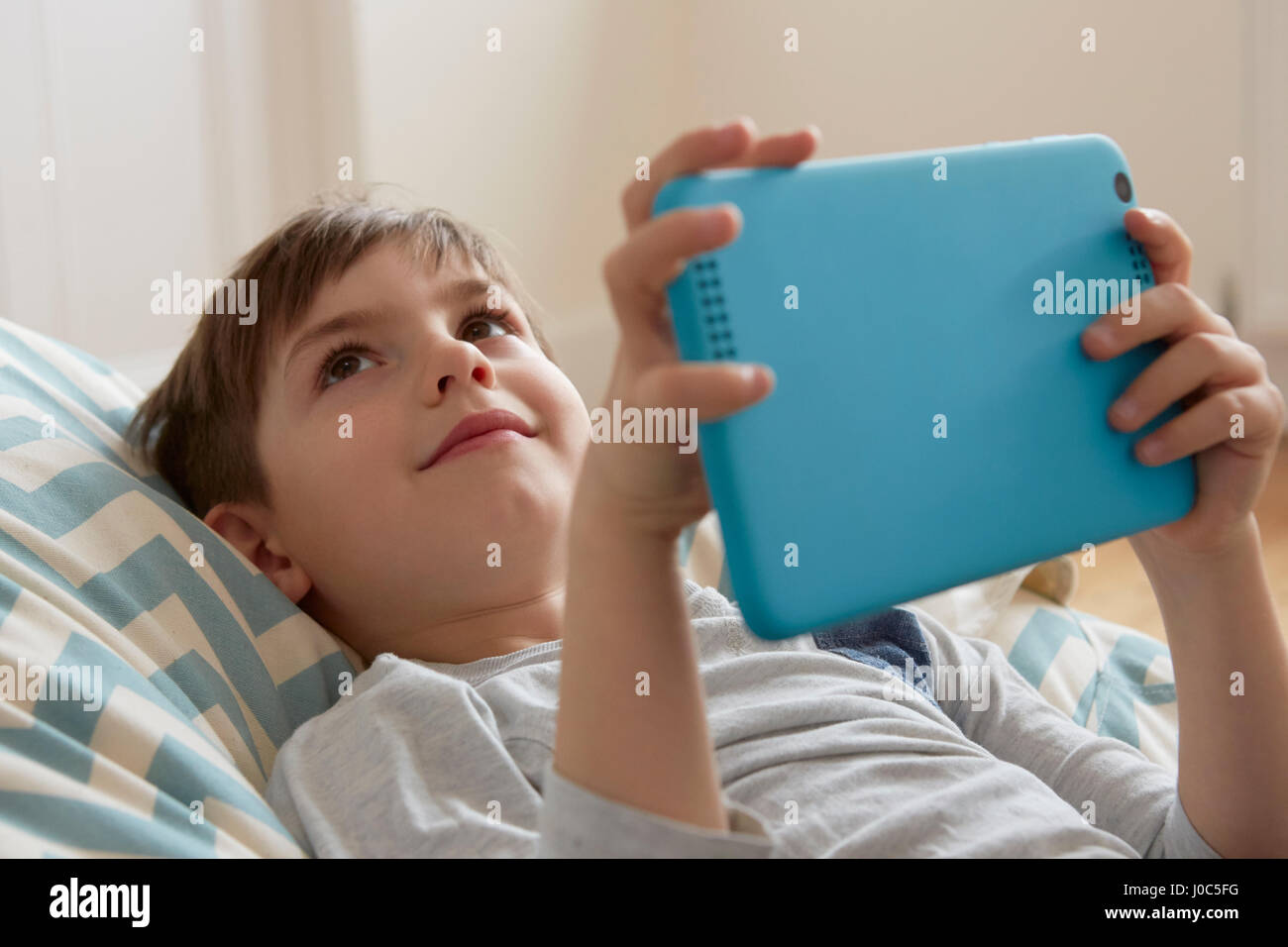 Boy reclining on beanbag chair looking up from digital tablet - Stock Image