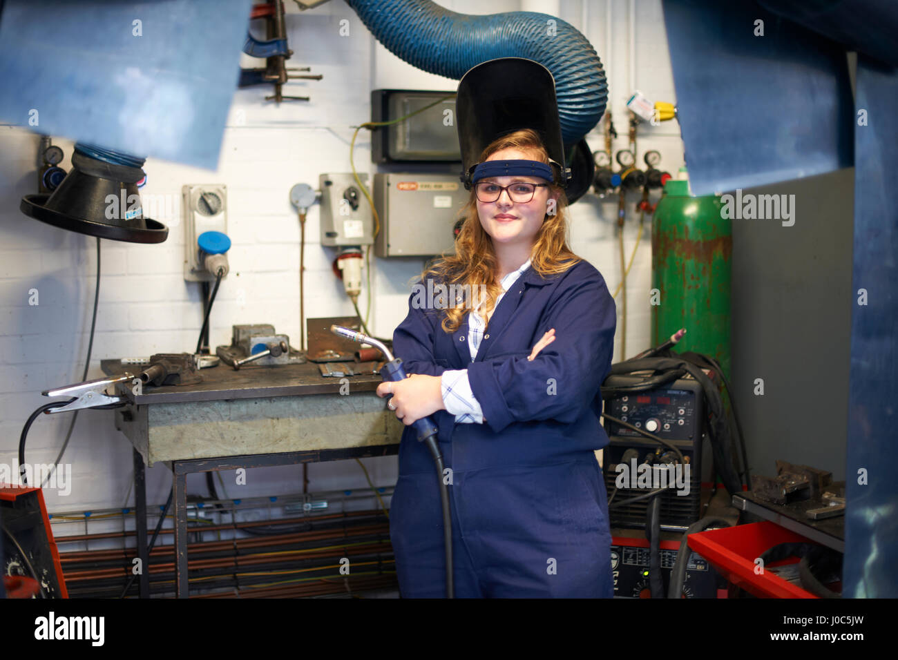 Portrait of female higher education student holding welding torch in workshop at college - Stock Image