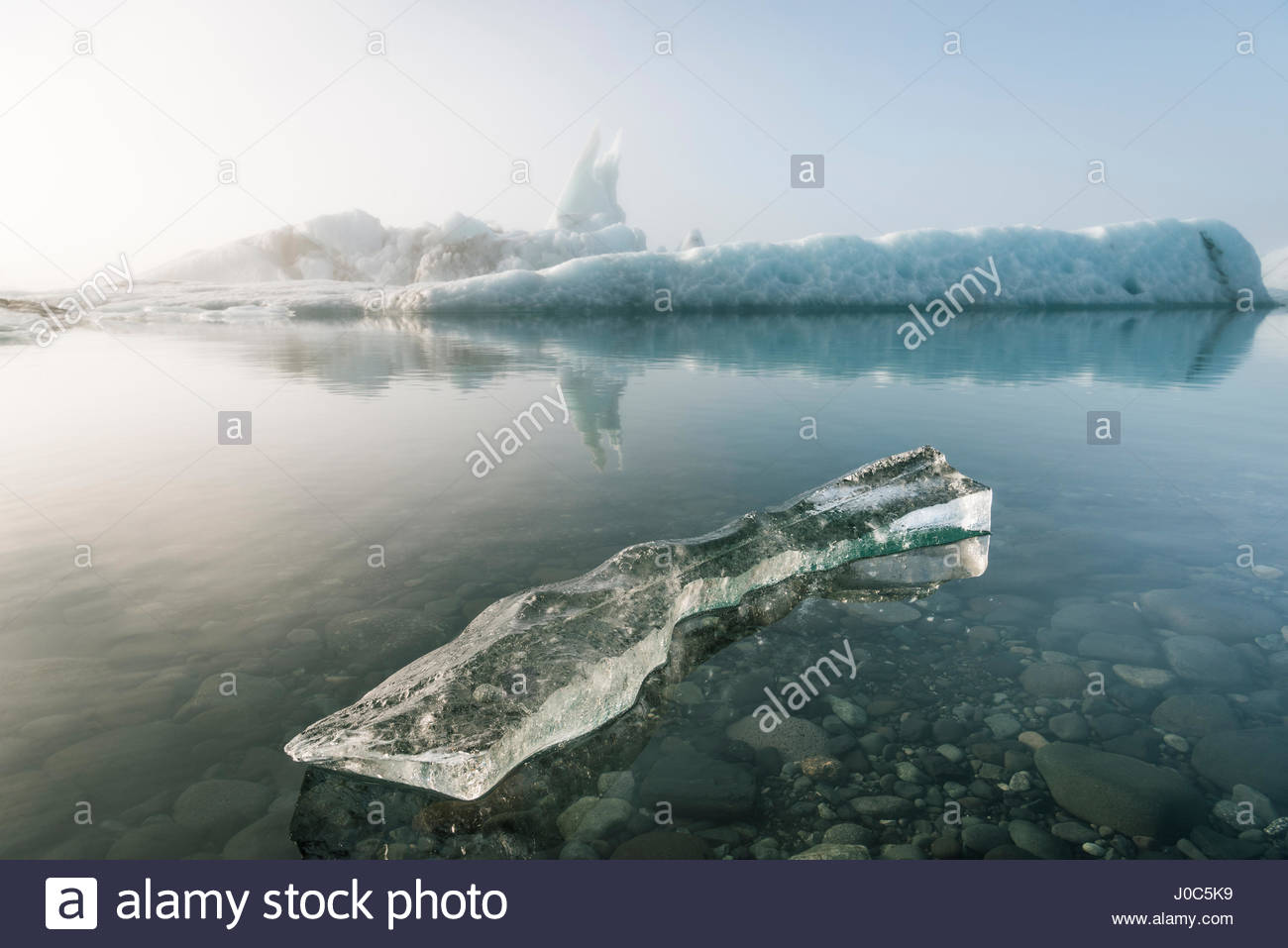 Misty view of ice bergs on glacial lagoon, Jokulsarlon, Iceland - Stock Image