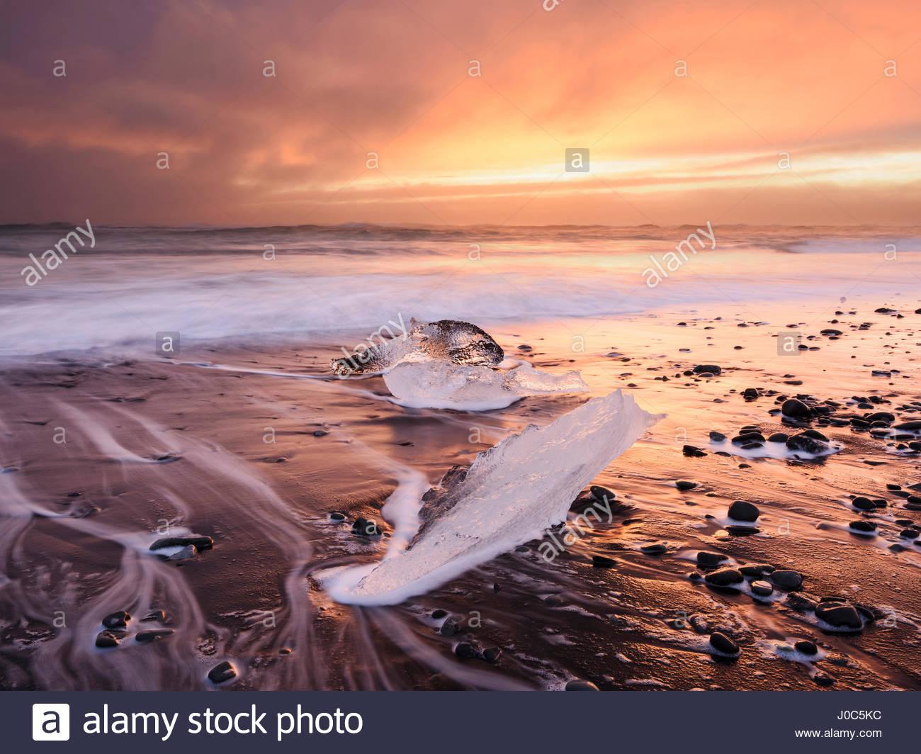Ice on glacial lagoon beach at sunset, Jokulsarlon, Iceland - Stock Image