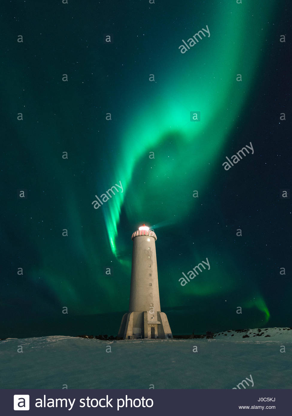 Aurora borealis swirling green over lighthouse at night,   Akranes, Iceland - Stock Image