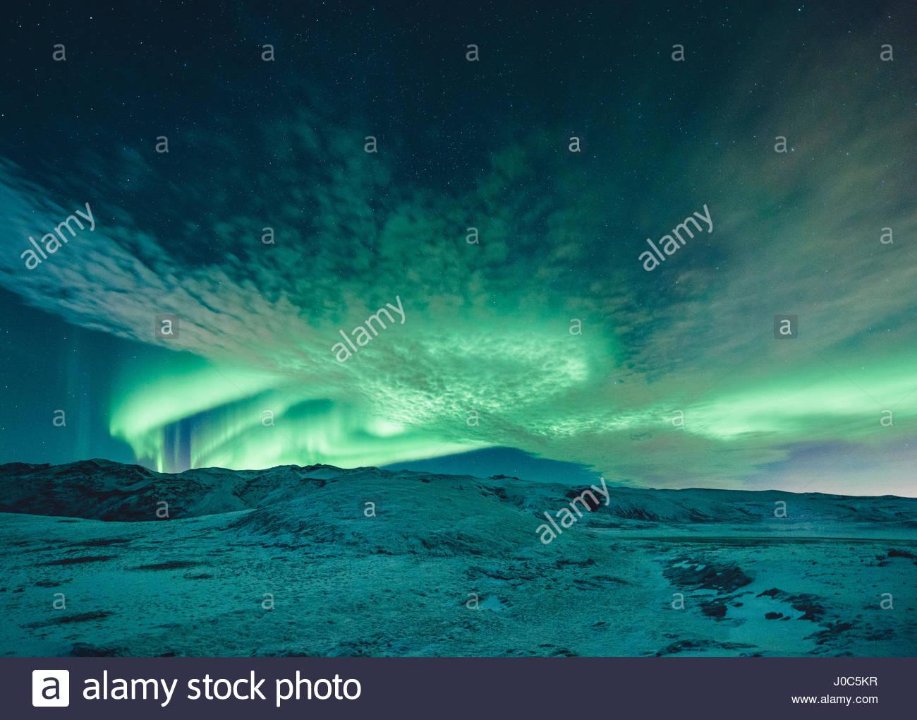 Aurora borealis swirling green over snow covered landscape, Lake Kleifarvatn, Iceland - Stock Image