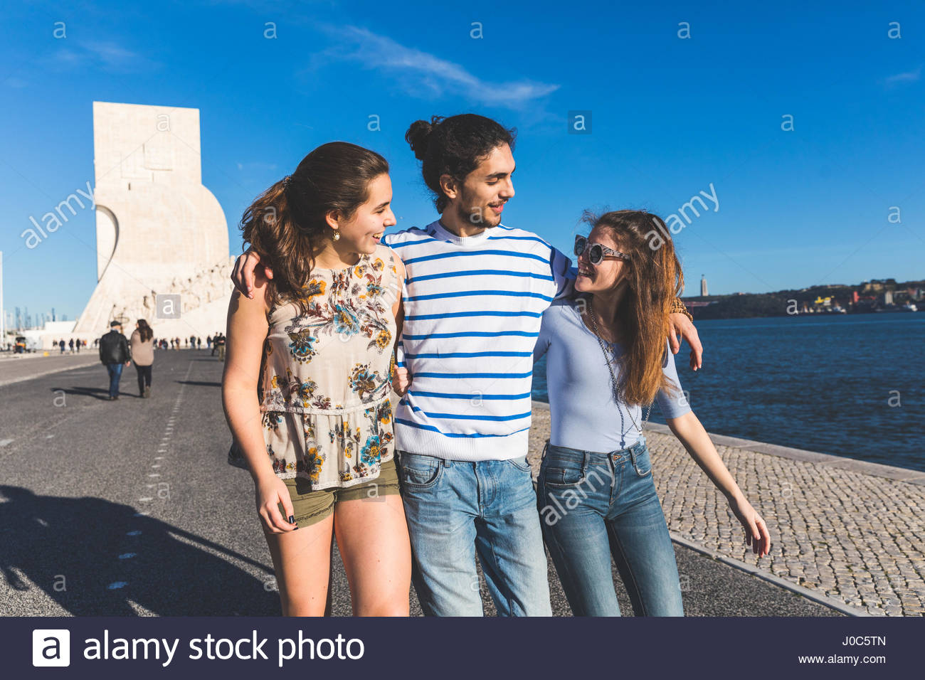 Three friends, walking by sea, Monument to the Discoveries in background, Lisbon, Portugal - Stock Image