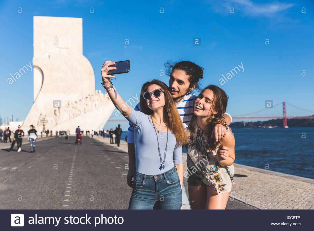 Three friends, outdoors, taking selfie with smartphone, Monument to the Discoveries in background, Lisbon, Portugal - Stock Image
