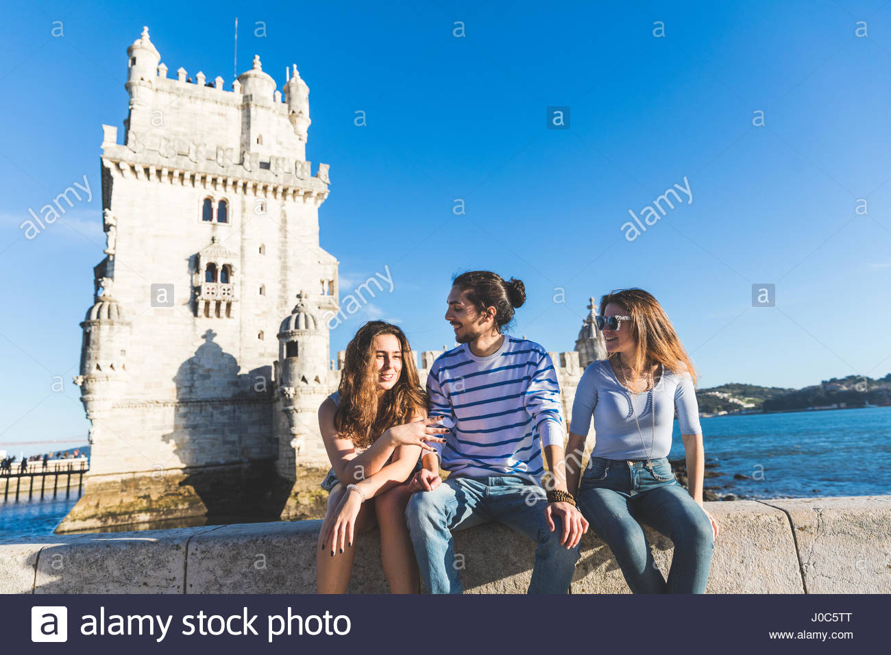 Three friends, sitting on wall by sea, Belem Tower in background, Lisbon, Portugal - Stock Image