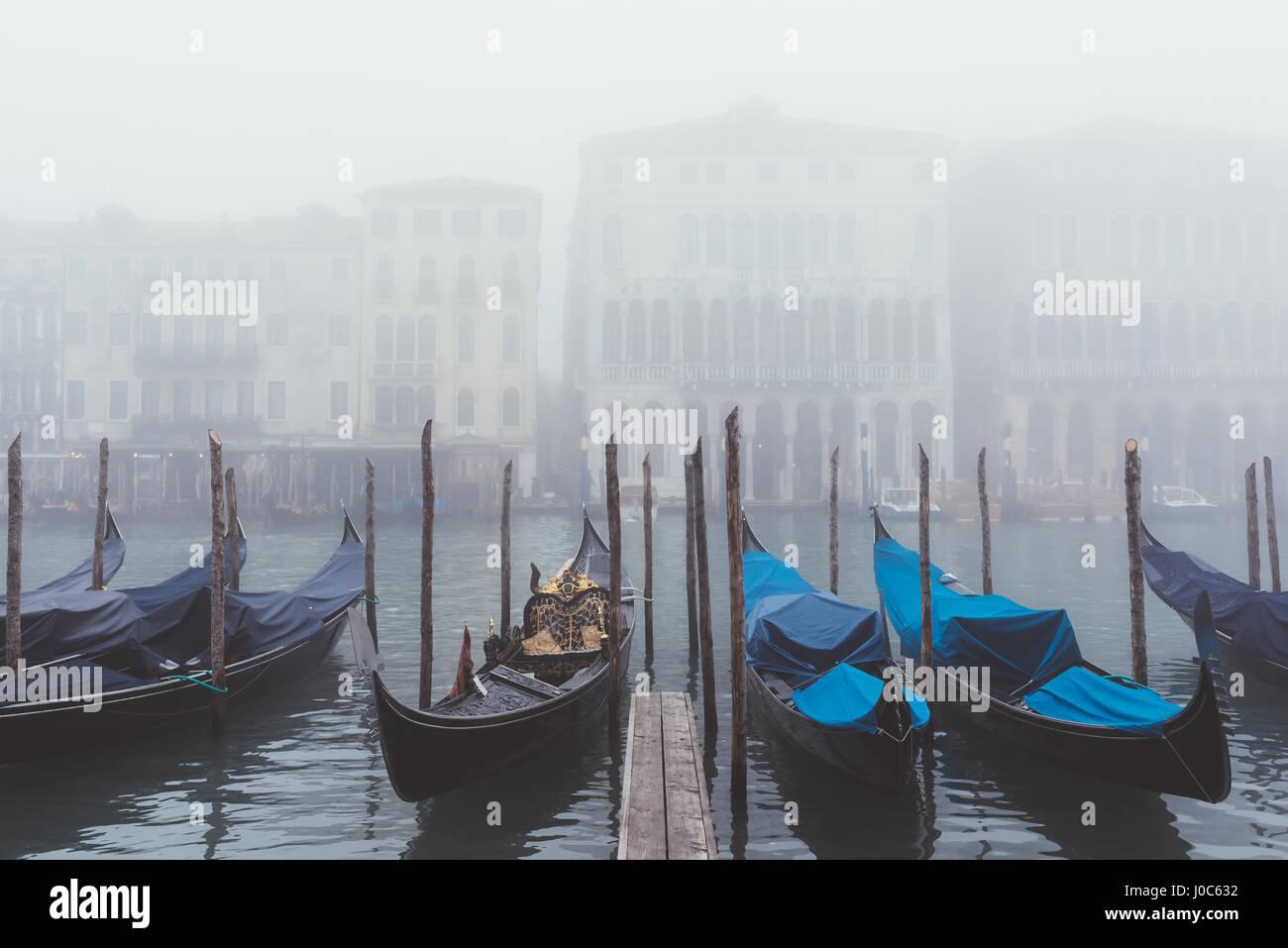 Rows of gondolas on misty canal, Venice, Italy - Stock Image
