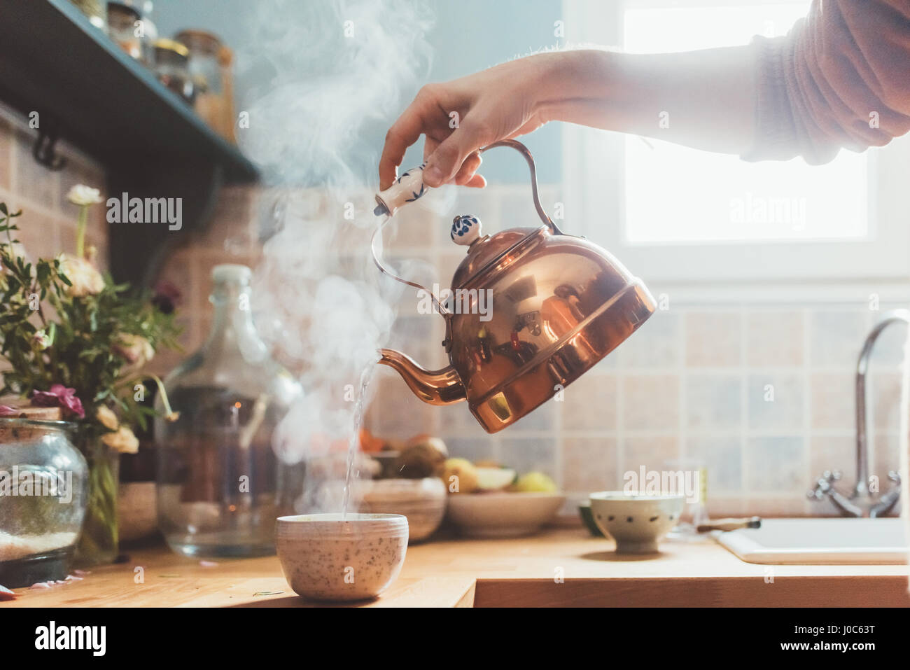 Arm of man pouring boiling water into bowl in kitchen - Stock Image
