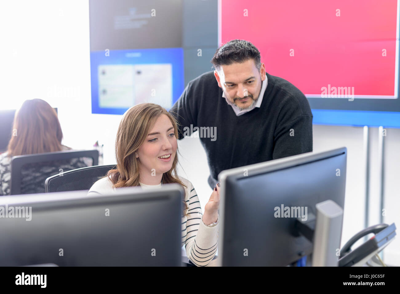 Office workers directing social media in call centre in car factory - Stock Image