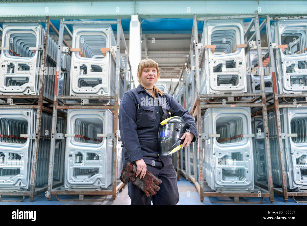 Female apprentice welder holding equipment in car factory, portrait - Stock Image