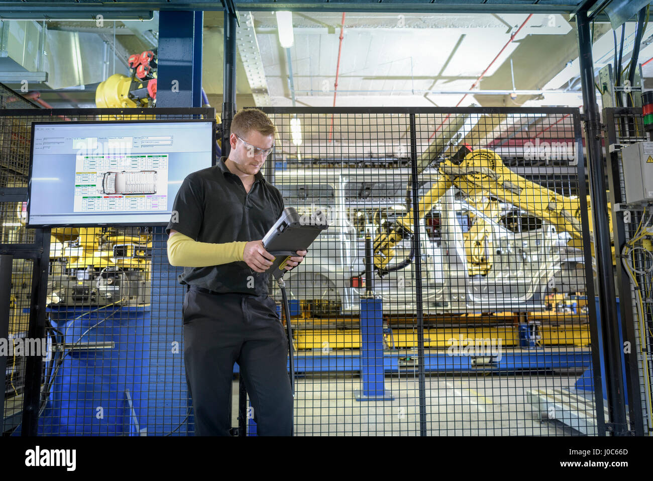 Apprentice engineer operating robots on production line in car factory - Stock Image