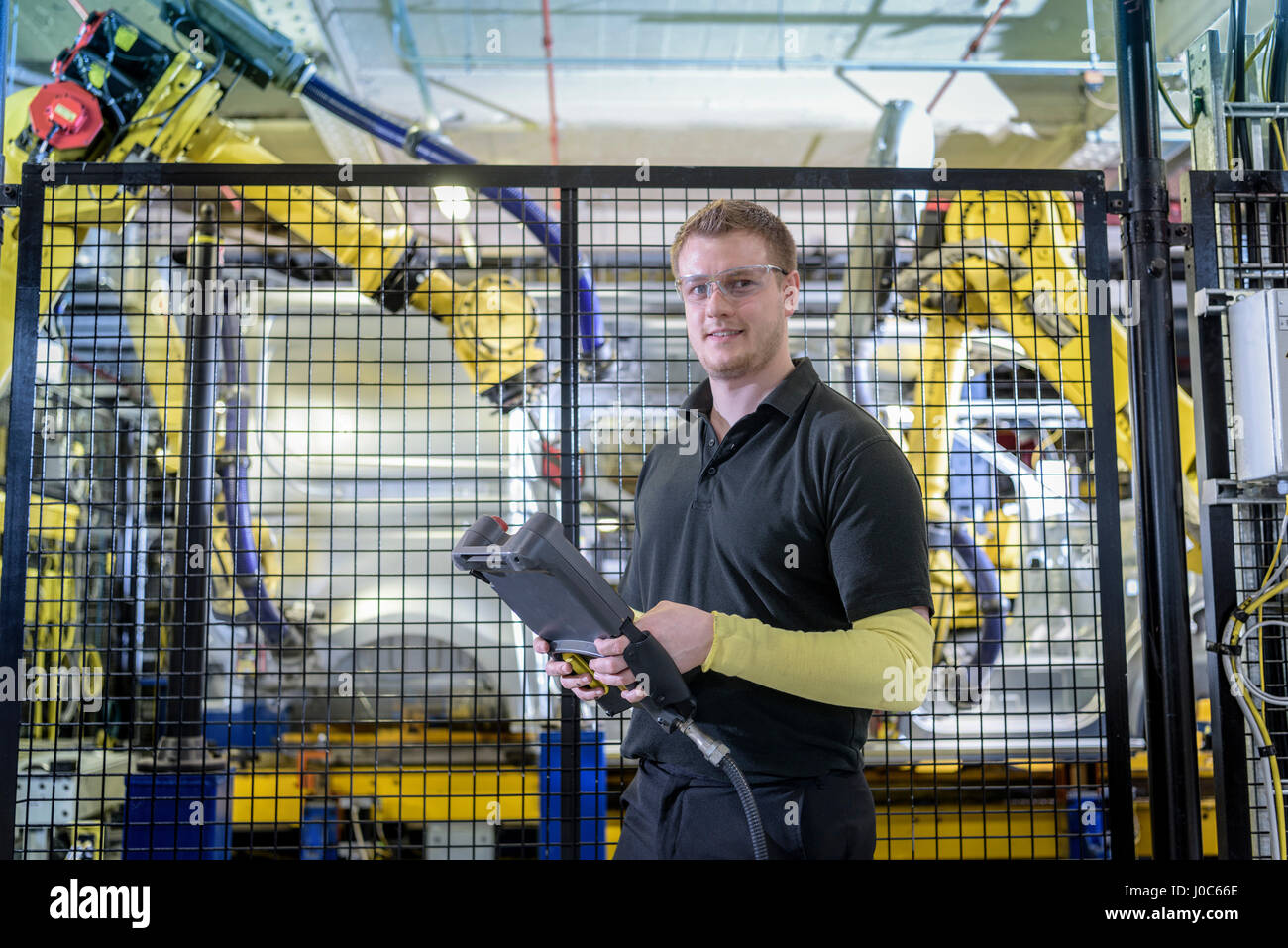 Portrait of apprentice engineer operating robots on production line in car factory - Stock Image