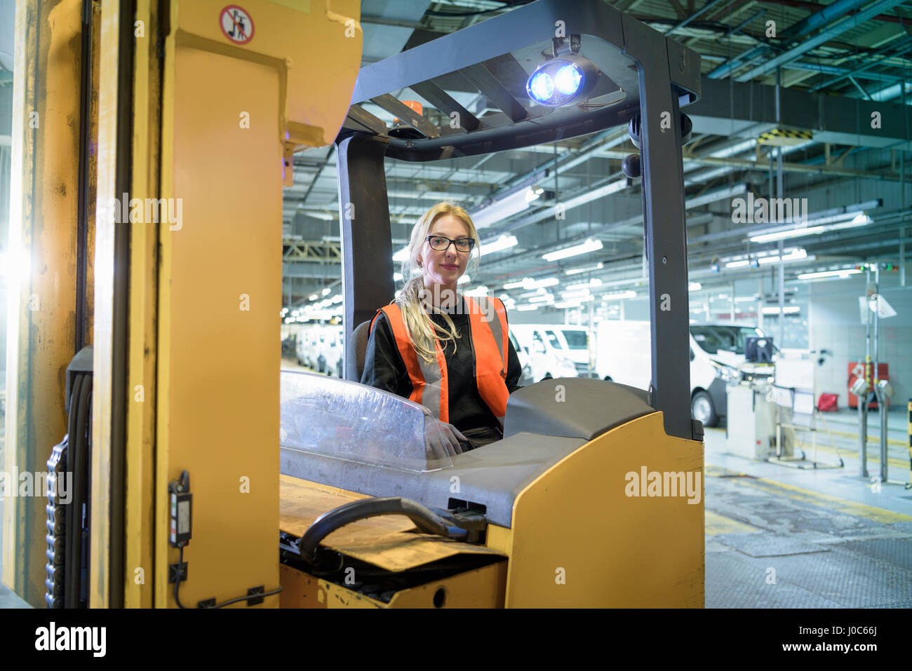 Portrait of female forklift driver in car factory - Stock Image