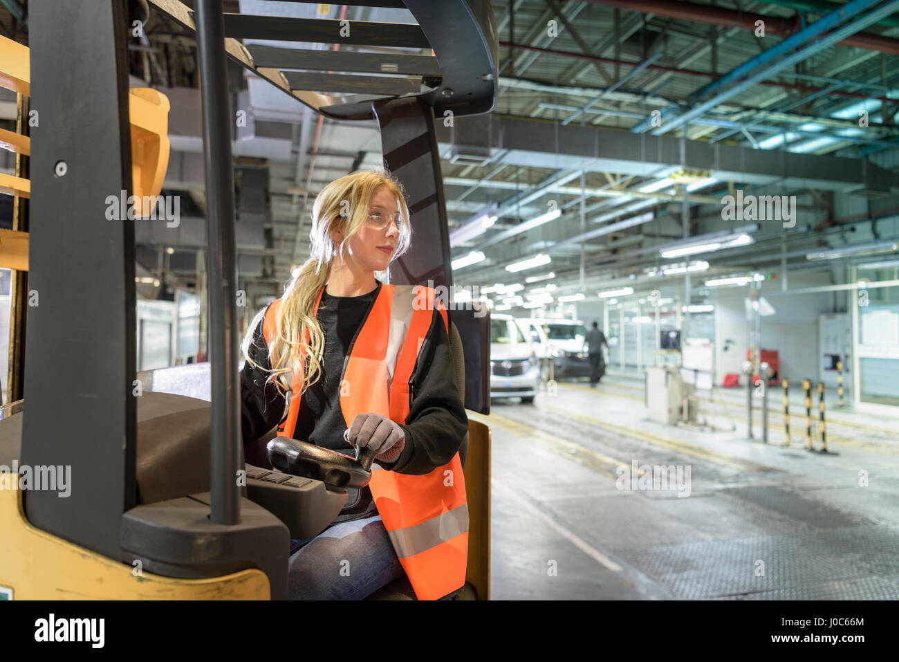 Female forklift driver in car factory - Stock Image