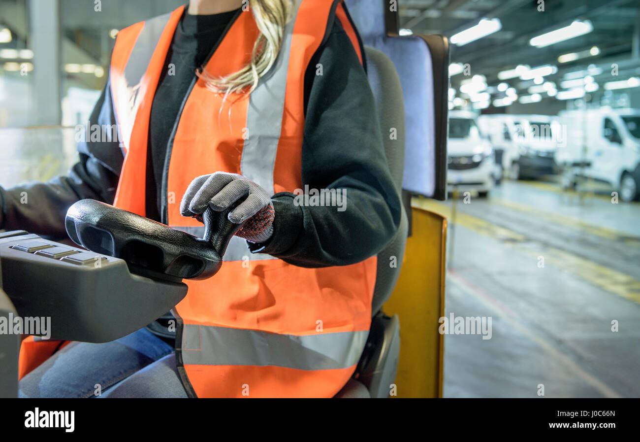 Female forklift driver in car factory, close up - Stock Image