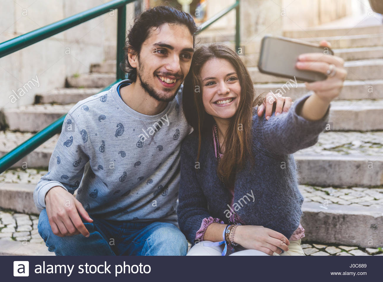 Young couple, sitting on steps, taking selfie with smartphone, Lisbon, Portugal Stock Photo
