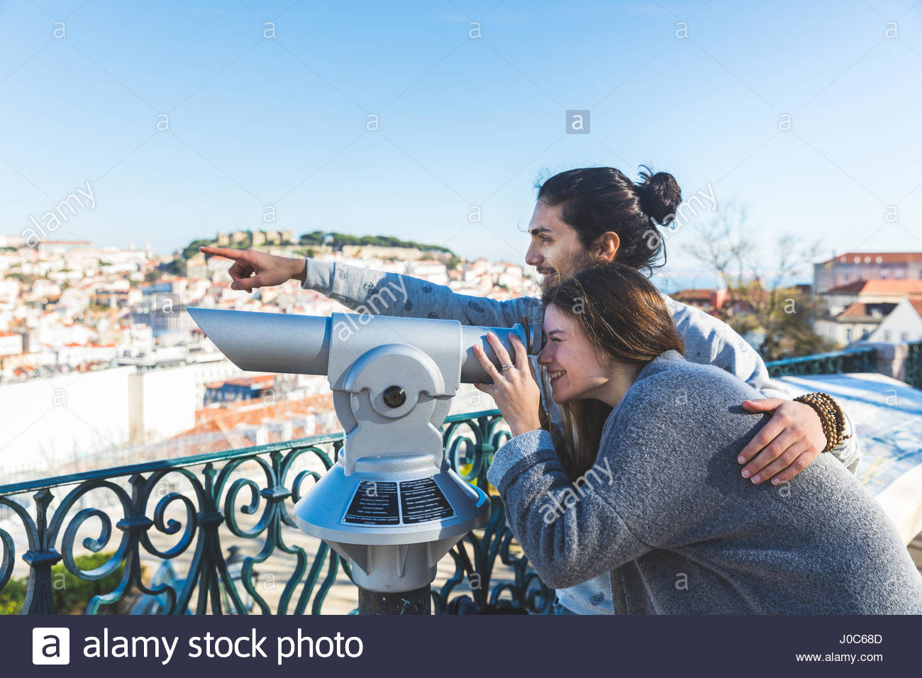 Young couple, sightseeing, looking through coin operated telescope, Lisbon, Portugal - Stock Image