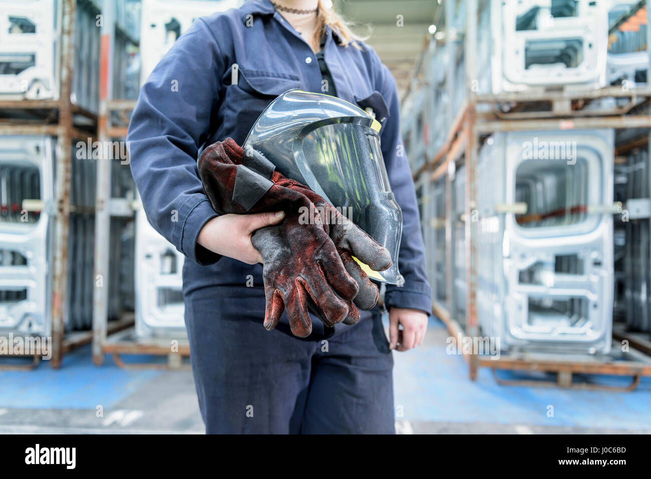 Female apprentice welder holding equipment in car factory - Stock Image