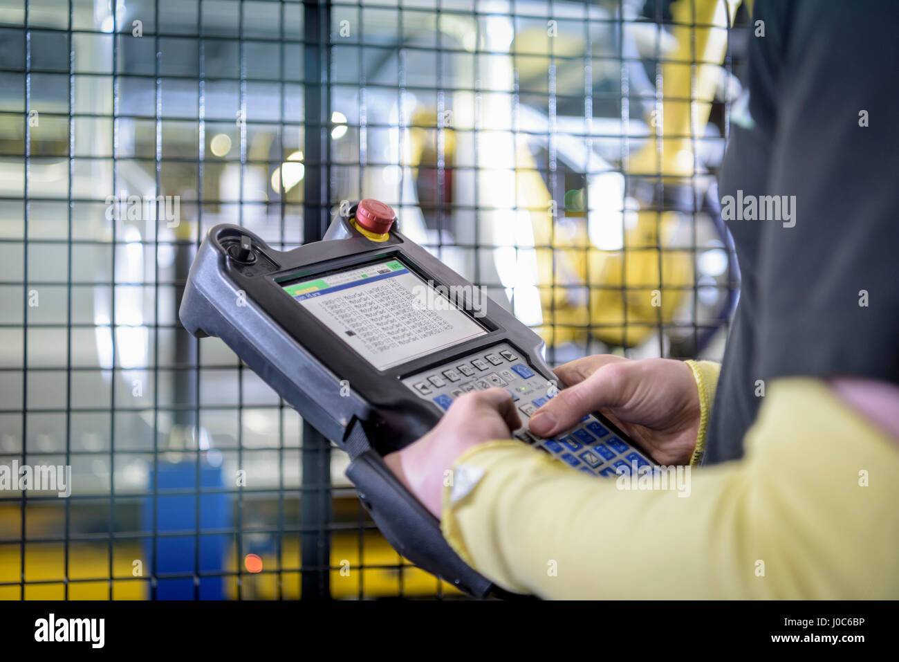 Apprentice engineer operating robots on production line in car factory, close up - Stock Image