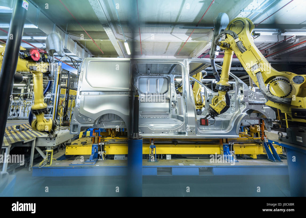 Vehicle and robots on production line in car factory - Stock Image