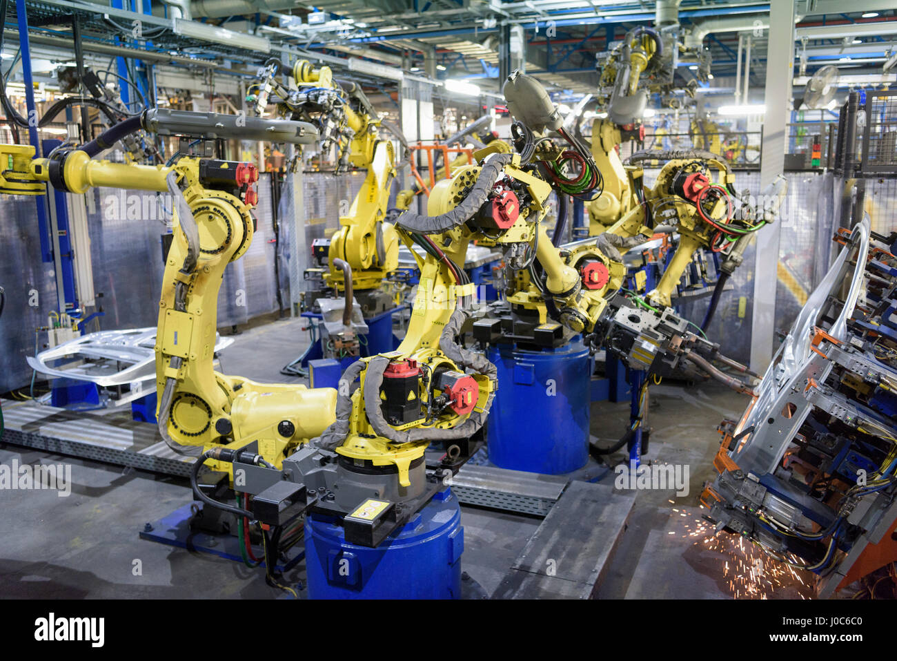 Robots welding body panels on production line in car factory - Stock Image