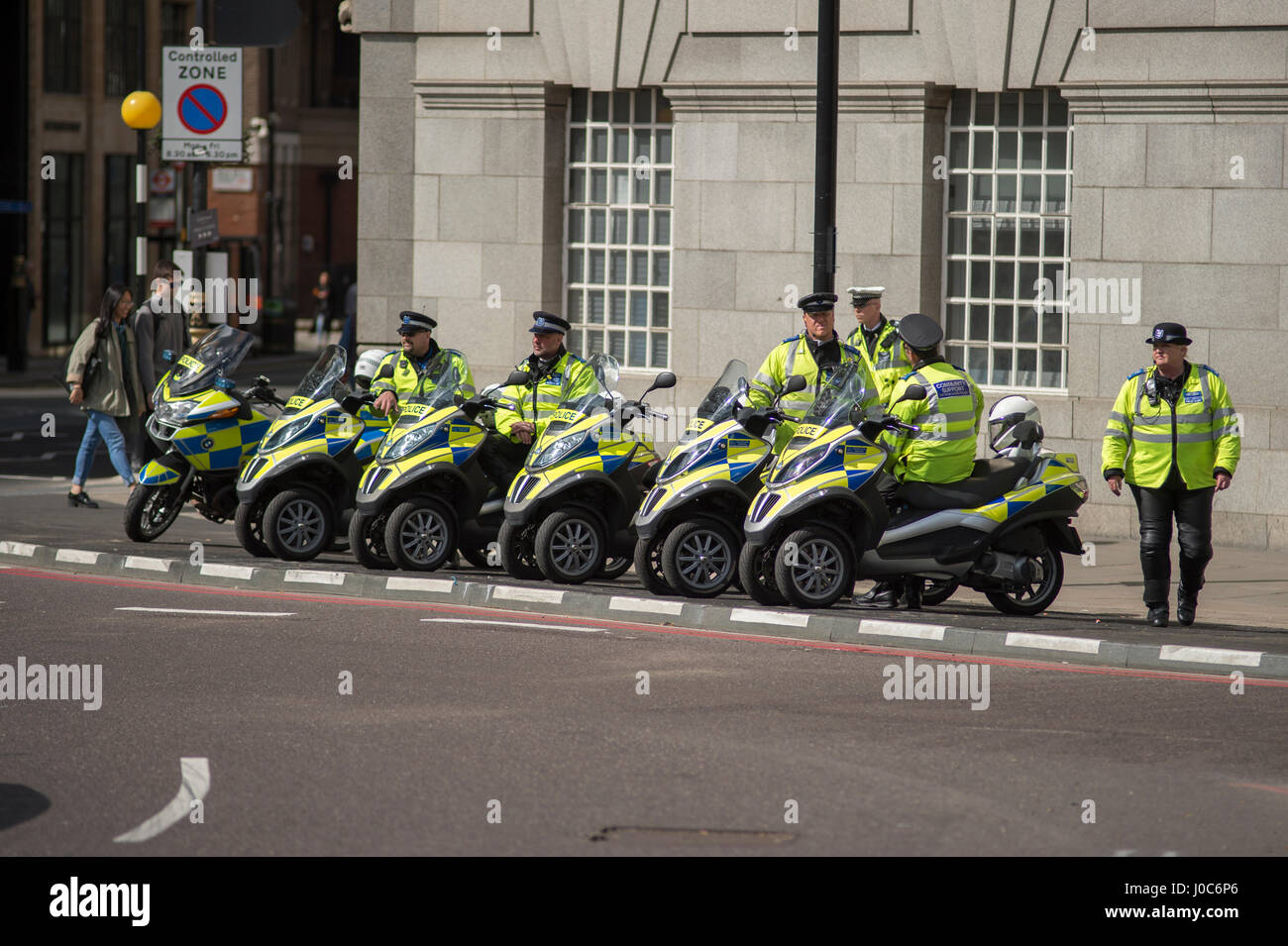 Police community support officers parked by roadside with three wheel scooters in Westminster at Millbank, London. - Stock Image
