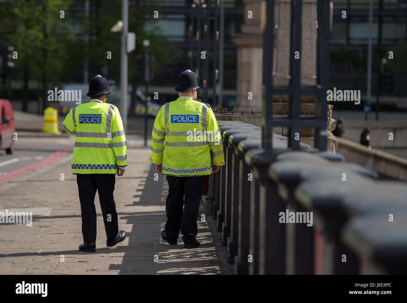 Metropolitan police officers walk along Lambeth Bridge in London wearing hi-viz vests. Credit: Malcolm Park - Stock Image