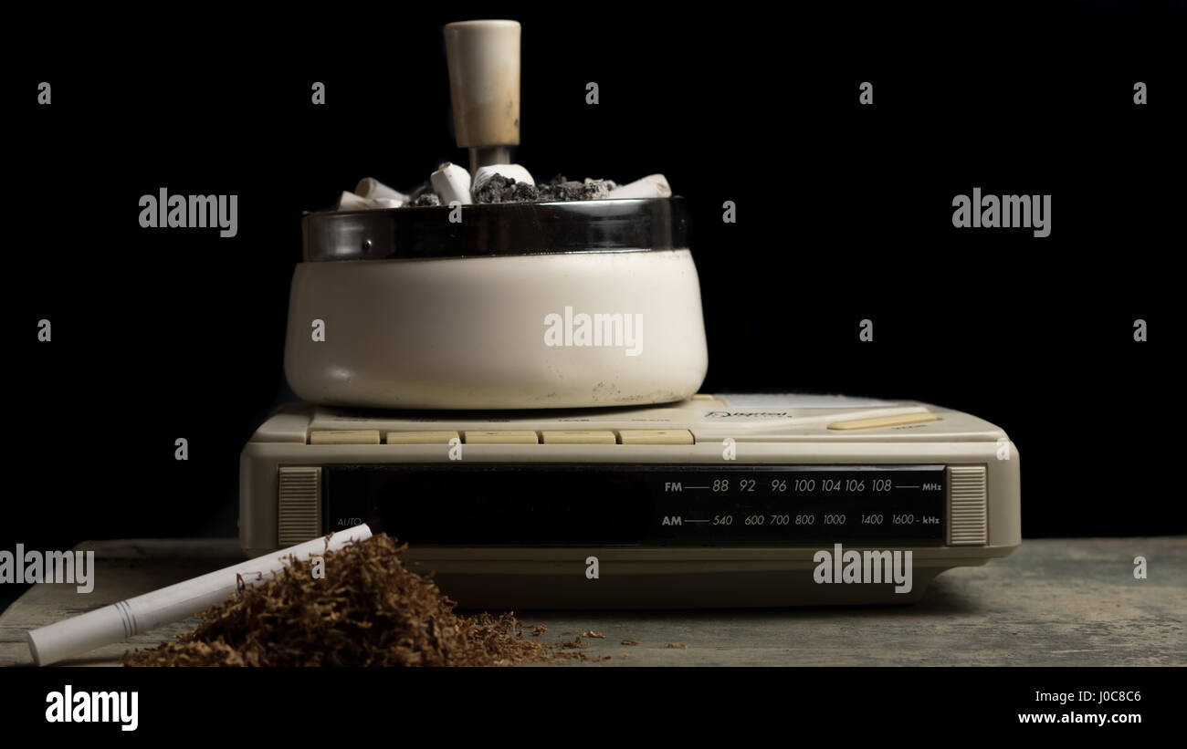 Ashtray with loads of cigarettes in it placed on a clock, addictive drugs. - Stock Image