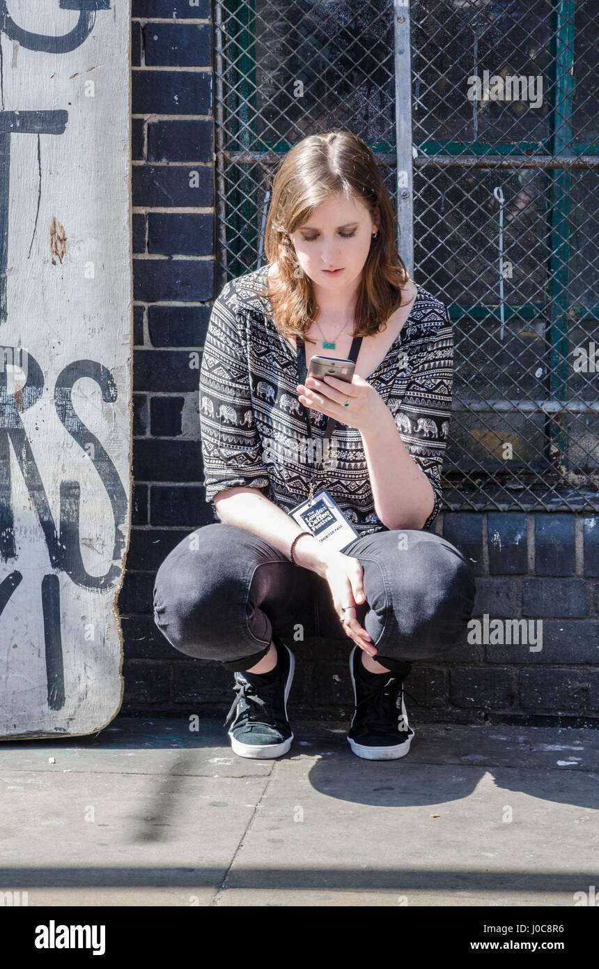 A lady takes a break outside, squatting down in the street to check her mobile phone. - Stock Image