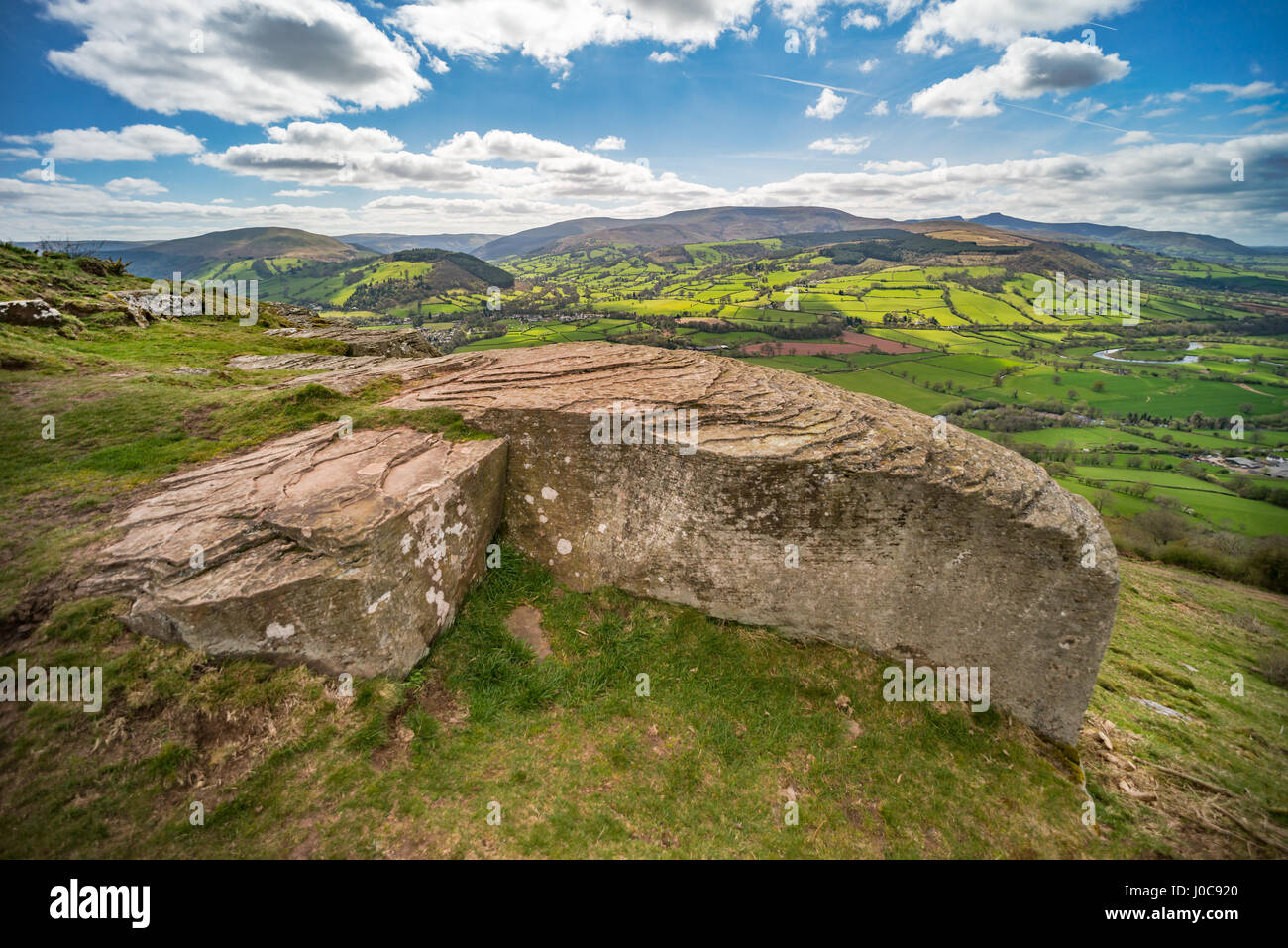 View over Usk valley to Brecon Beacons from Allt yr esgair hillside. Large rock with rippled pattern in foreground. - Stock Image