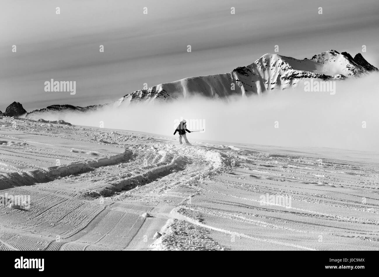 Snowboarder downhill on off-piste slope with newly-fallen snow. Region Gudauri, Caucasus Mountains, Georgia. Black - Stock Image