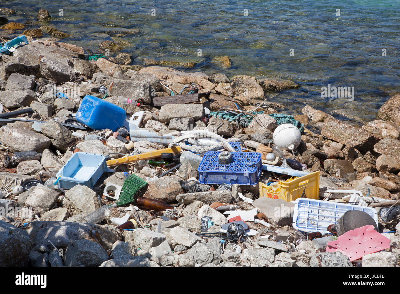 Plastic and glass marine debris washed ashore in the harbor of a North Pacific island - Stock Image