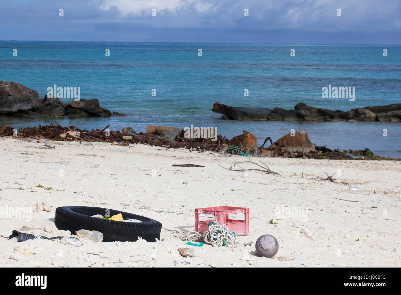 Trash including tire, plastic water bottle, box and ropes washed ashore on the beach of a North Pacific island - Stock Image