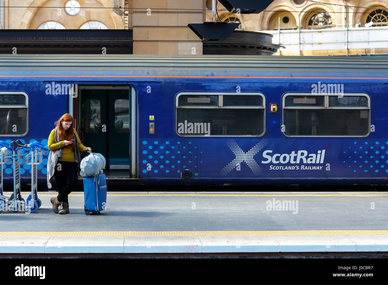 Woman waiting on platform at Glasgow Central railway station, Glasgow with a Scotrail carriage behind her. Glasgow, - Stock Image