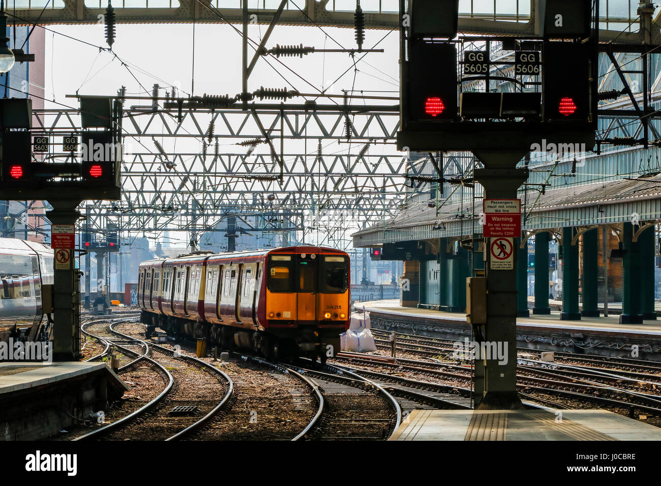 Train approaching a platform at Glasgow Central railway station, Glasgow, Scotland, UK - Stock Image