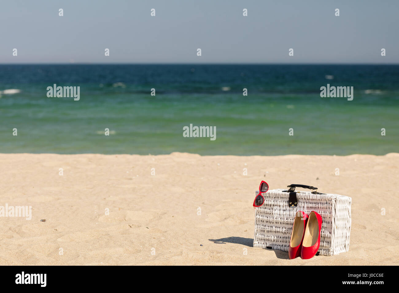 Summer vacation at sea. White wicker suitcase and women's accessories and shoes on the beach. Selective focus. - Stock Image