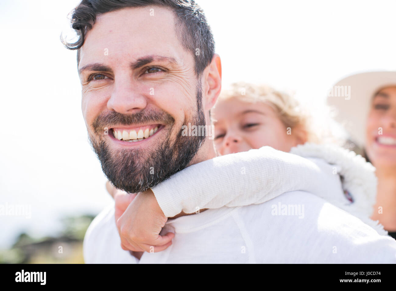 Girl having piggy back from father at coast - Stock Image