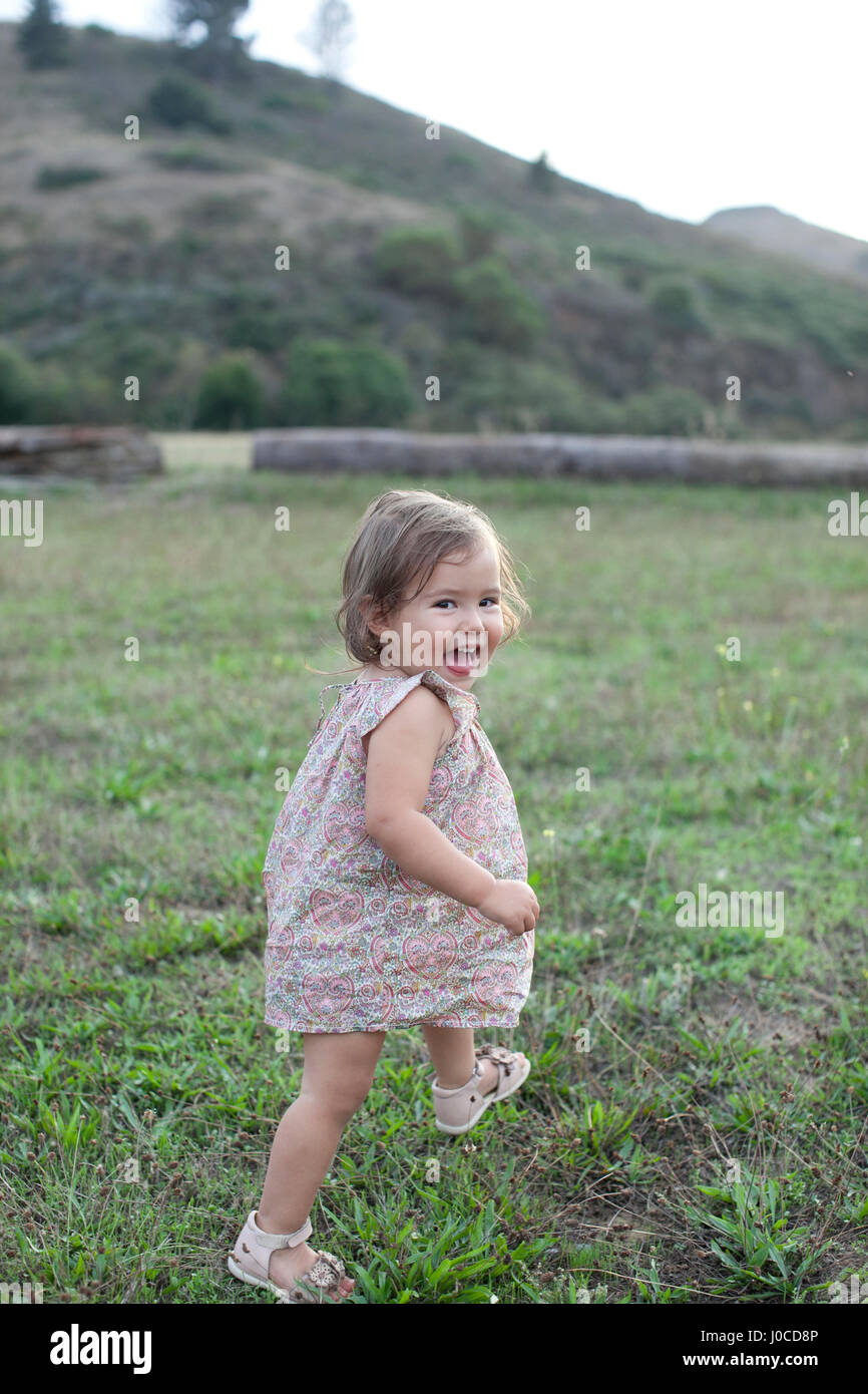 Cute female toddler running in field looking over her shoulder - Stock Image e3cadf430534