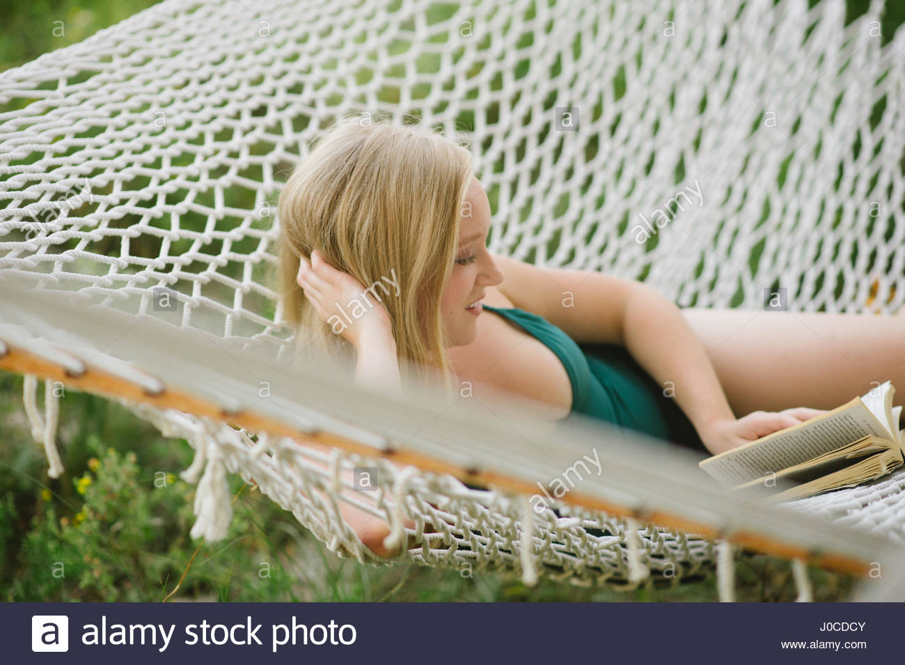 Young woman reading book on beach hammock - Stock Image