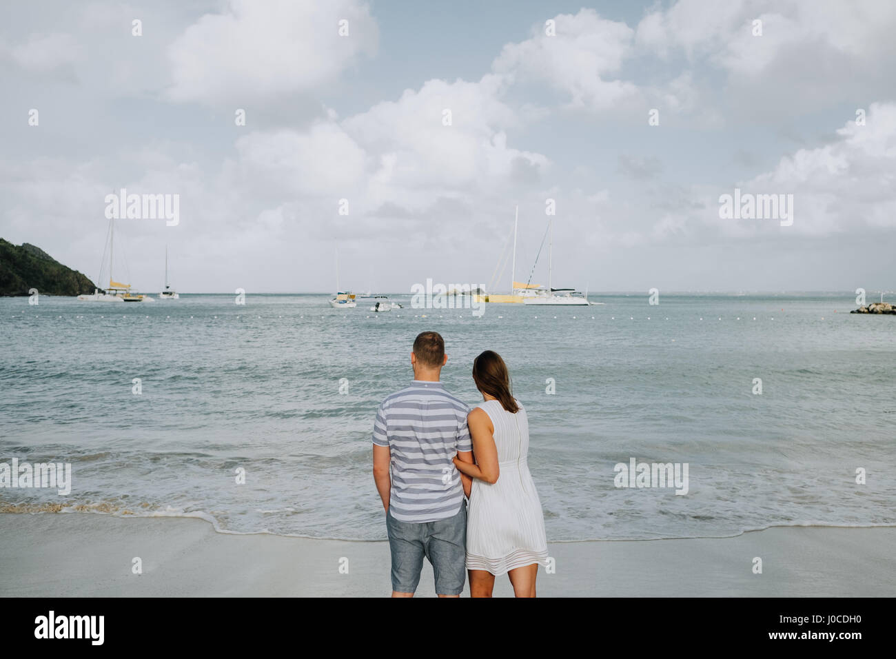 Couple standing, looking out to sea, rear view, Saint Martin, Caribbean - Stock Image