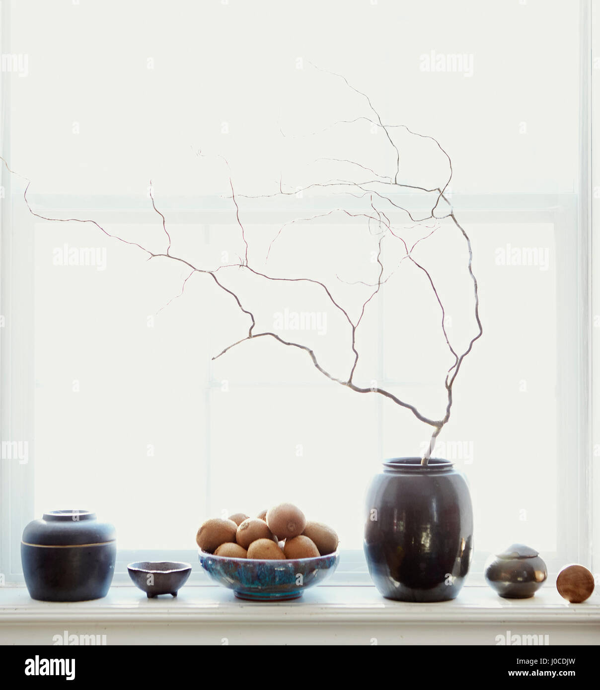 Composition of fruits and vases by window - Stock Image