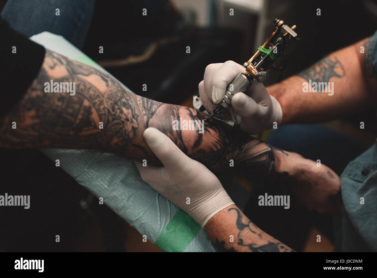 Tattooist tattooing young man's arm, close-up - Stock Image