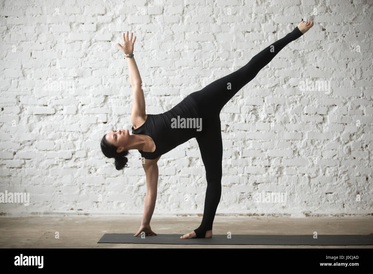 Young yogi attractive woman in Half Moon pose, loft background - Stock Image