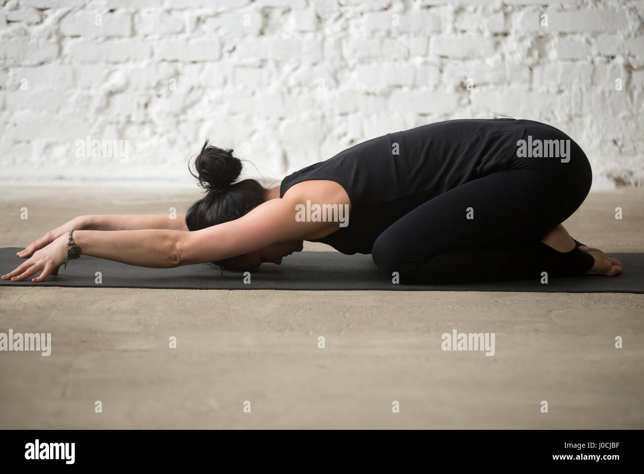 Young yogi attractive woman in Child pose, white loft background - Stock Image