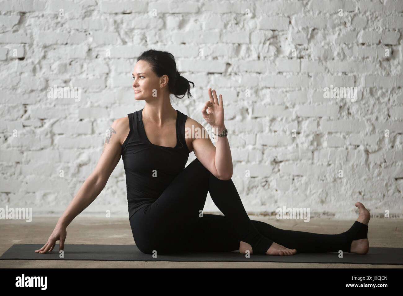 Young yogi attractive woman in Ardha Matsyendrasana pose, white  - Stock Image