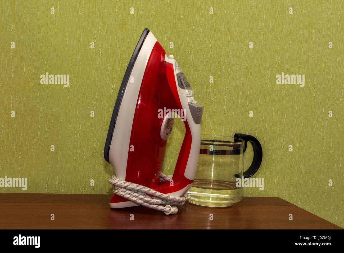 Iron red for ironing clothes on a brown table against a green wall. Stock Photo