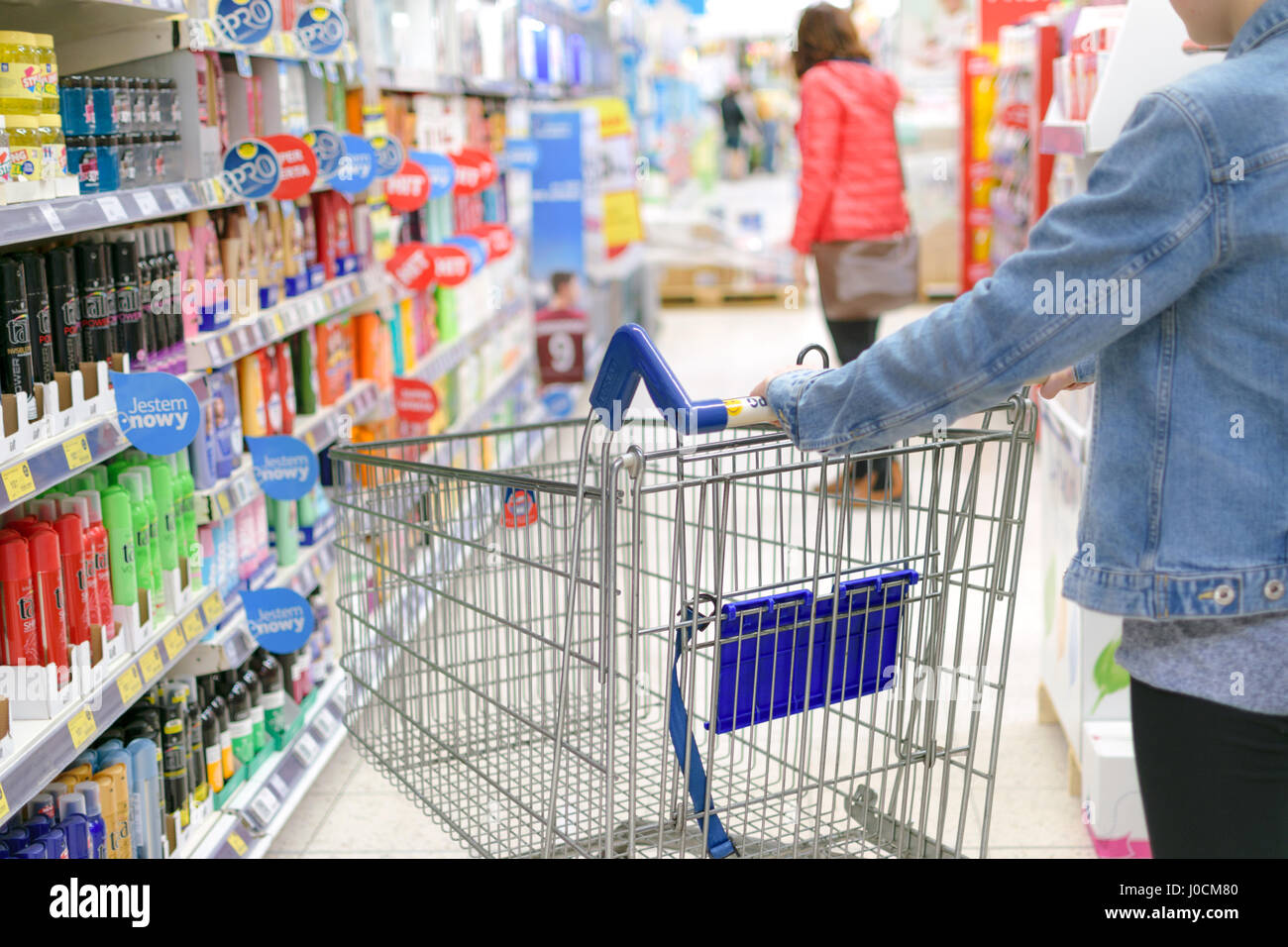 Nowy Sacz, Poland - March 29, 2017: Young woman pushing shopping cart through front of aisle with a variety of personal - Stock Image