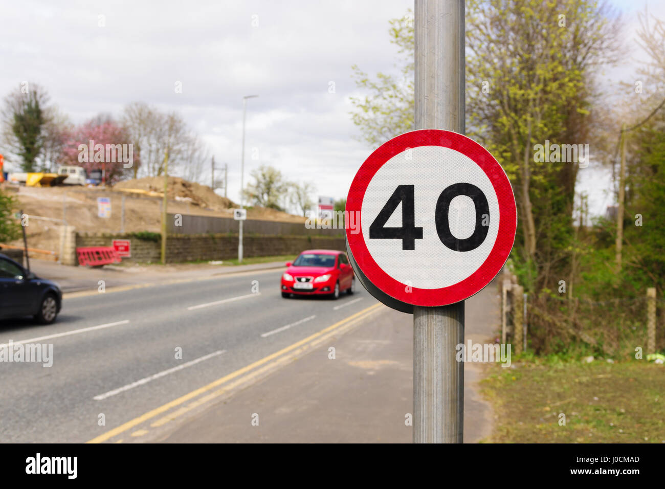 Urban 40 miles per hour speed limit sign used in the United Kingdom with defocussed traffic in the background - Stock Image